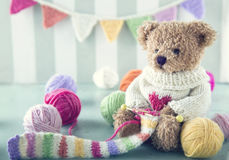 Teddy bear in a woolen sweater. Knitting a striped scarf with colorful balls of yarn stock photography