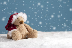 Teddy bear with xmas hat seated in the snow Royalty Free Stock Photography