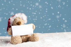 Teddy bear with xmas hat seated in the snow Stock Photos