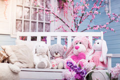 Teddy bears, Bunny and plush poodle sitting on white wooden bench. Blooming oriental cherry at the background. Friendship and childhood symbols Royalty Free Stock Image