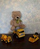 Teddy Bears classique contre un mur bleu et véhicules classiques de construction Photo libre de droits