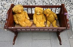 Teddy bears in cradle. Three teddy bears in cradle on the antiques fair Royalty Free Stock Images