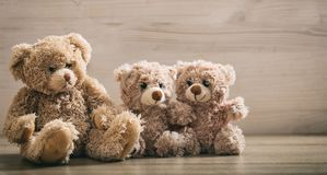 Teddy bears family sitting on a wooden background Royalty Free Stock Image