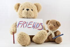 Teddy bears friendship. Two teddy bears with word friends on paper Stock Photo