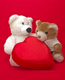 Teddy bears with gift box in a heart shape. Two teddy bears with gift box in a heart shape Royalty Free Stock Images