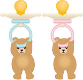 Teddy bears holding pink and blue baby pacifiers Stock Photo