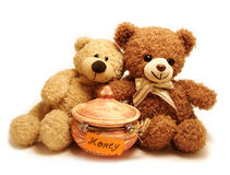 Teddy-bears & honey. Two teddy-bears sitting near the pot with honey Royalty Free Stock Photography