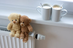 Teddy bears on radiator. Two teddy bears sitting on radiator in home, with coffee cups on windowsill