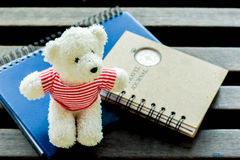 Teddy bears sitting on a book at wooden table  Stock Image