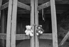 Teddy Bears Sitting On Derelict Fie Station Bay Doors In Black & White Stock Images