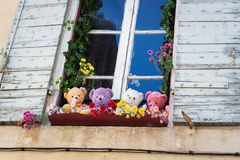 Teddy bears sitting on the windowsill. Vintage style teddy bears sitting on the windowsill in a romantic city in Provence Royalty Free Stock Images