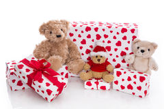 Teddy bears surrounded by Christmas gift boxes on white backgrou Stock Photo
