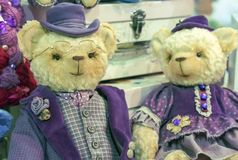 Teddy bears in vintage purple hats and outfits stock images