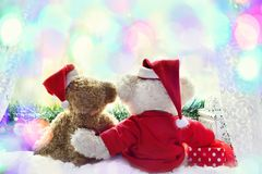 Teddy bears waiting for fairy christmas time. Two cute teddy bears in santa hats sitting back on the window sill and waiting for fairy colorful christmas time Royalty Free Stock Photography