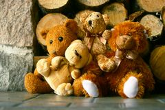 Teddy bears and woodpile. Four fuzzy teddy bears sitting in front of a woodpile Royalty Free Stock Images