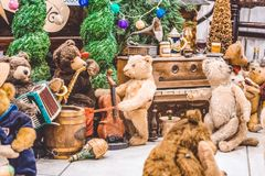 Teddy brown bears are busy with commonplaces. Exhibition of toys. A party with a piano on New Years Eve. Statement. stock photos