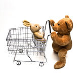 Teddy and Cart. Plush teddy bear pushing a metal shopping cart with a rabbit in the seat Stock Photos
