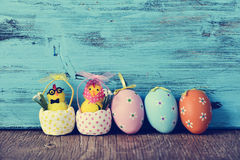 Teddy chicks and easter eggs. A funny couple of teddy chicks, a male and a female, and some different ornamented easter eggs on a wooden surface, against a blue Royalty Free Stock Images