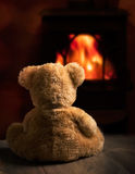 Teddy By The Fire Stockbild