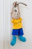 Teddy hanging at door handle Stock Photography