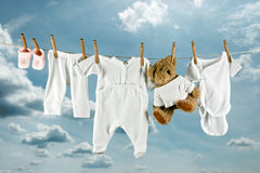 Teddy and laundry. Cute teddy bear hanging outside between baby laundry Royalty Free Stock Photography
