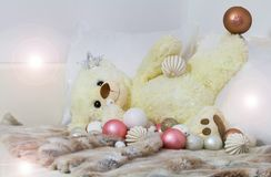 Soon will be Christmas again. The teddy plays with the Christmas balls Stock Photo
