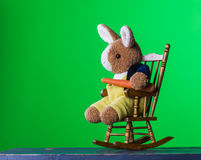 Teddy rabbit with carrot sitting on the rocking chair. Stock Images