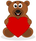 Teddy sat smiling with a heart Stock Photo