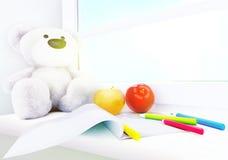 Teddybär, Äpfel, Album und Bleistifte auf dem Fensterbrett Stockfotografie