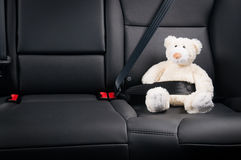 Teddybär befestigte sich im Rücksitz eines Autos Stockfotografie