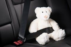 Teddybär befestigte sich im Rücksitz eines Autos Stockfotos