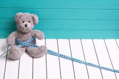 Teddybär betreffen einen blaugrünen Hintergrund des weißen Bretterbodens mit Zentimeter Diät und Gewichtsverlust in den Kindern Stockbild