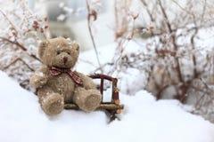 Teddybär, der auf einer Bank im Schnee sitzt Stockfotografie