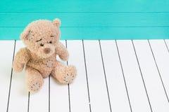 Teddybär, der auf weißem Bretterboden mit dem blaugrünen Hintergrund einsam sitzt Lizenzfreies Stockfoto