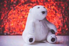 Teddybär, der auf weißem Bretterboden mit nettem bokeh Hintergrund sitzt Stockfoto