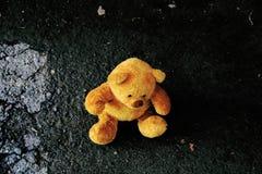 Teddybär, der aus den Grund sitzt stockbild
