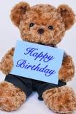 Teddybär, der das blaue Zeichen sagt alles Gute zum Geburtstag hält Lizenzfreies Stockbild