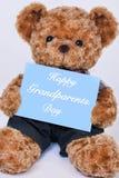 Teddybär, der das blaue Zeichen sagt glücklichen Großeltern-Tag hält Lizenzfreie Stockfotografie