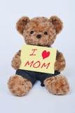 Teddybär, der ein gelbes Zeichen hält, das i-Liebesmutter sagt Lizenzfreie Stockbilder