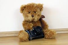 Teddybär, der eine Kamera anhält stockfotografie