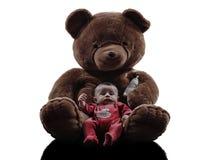 Teddybär, der sitzendes Schattenbild des Babys umarmt Stockbild