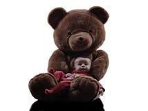 Teddybär, der sitzendes Schattenbild des Babys umarmt Stockfotos