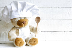 Teddybär im Chefhut mit Löffelzusammenfassungs-Lebensmittelhintergrund Lizenzfreies Stockbild