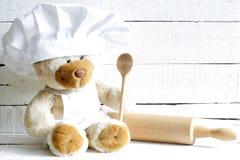Teddybär im Chefhut mit Löffelzusammenfassungs-Lebensmittelhintergrund Lizenzfreie Stockfotos
