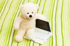 Teddybär mit einem Laptop Stockbild