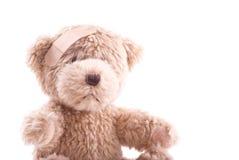 Teddybär mit einem Owie Stockbild