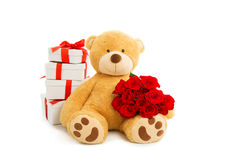 Teddybär mit Geschenkbox und Blumenstrauß von roten Rosen Lizenzfreies Stockbild