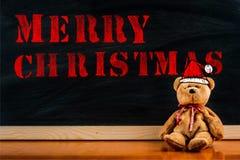 Teddybär mit Hinweissymbol und Mitteilung ` frohe Weihnachten ` Stockbild