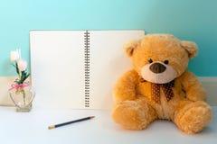 Teddybär mit Notizbuch der rosa Blume und der Leerseite mit Bleistift Lizenzfreies Stockfoto