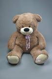 Teddybär mit Schal auf grauem Hintergrund stockfotos